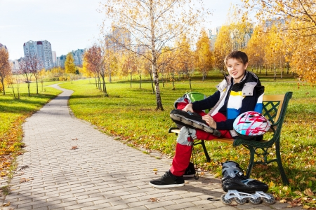 Happy smiling 10 years old boy sitting on the bench in autumn park and putting on roller blades photo