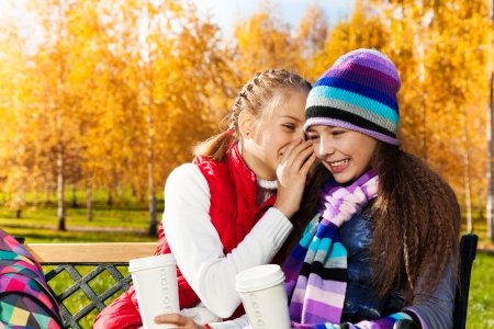 11 years old: Two happy girls whispering 11 years old sitting on the bench in autumn park Stock Photo
