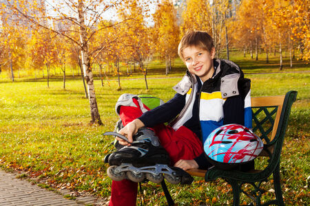 10 years old: 10 years old boy sitting on the bench in autumn park getting ready to skate outside Stock Photo