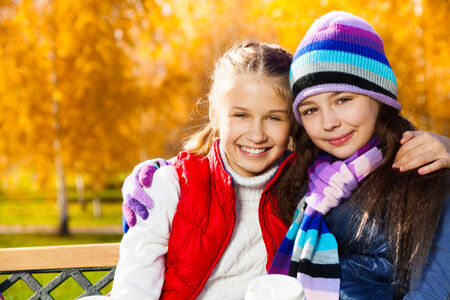 Close portrait of two happy smiling laughing and hugging girls 11 years old sitting on the bench in autumn park photo