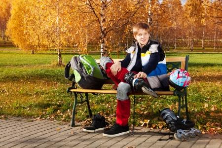 niño en patines: 10 años de edad niño de la escuela que se sienta en el banco en el parque de otoño con patines Foto de archivo