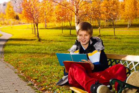 10 month: 10 years old boy sitting on the bench in autumn park with smile on the on his face and reading from textbook