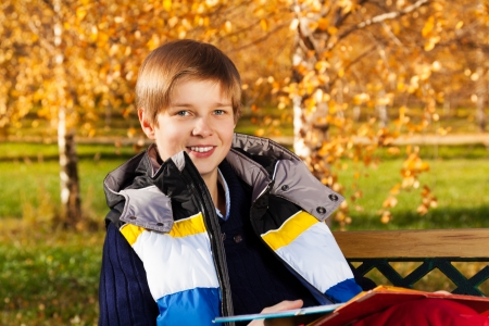 10 month: Close portrait of 10 years old boy sitting on the bench in autumn park Stock Photo