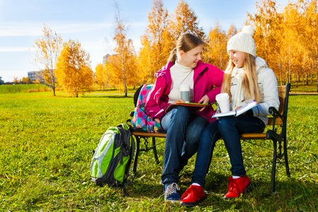 Two happy 14 years old girls in the autumn park chatting holding text books and coffee mugs photo