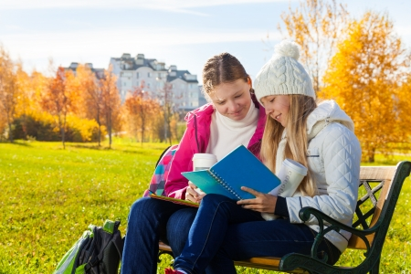 Two happy 14 years old girls in the autumn park taking about homework holding textbook and coffee photo