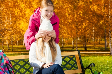 guess: Two happy 14 years old girls in the autumn park playing guess who am I Stock Photo