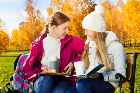 Two happy 14 years old girls in the autumn park with coffee and books sitting on the bench and looking on each other photo