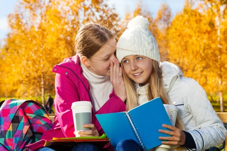 Two happy 14 years old girls whispering secrets and gossips in the autumn park sitting on the bench  holding textbook and coffee photo