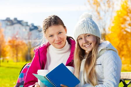 Close portrait of two happy 14 years old girls in the autumn park with textbook and coffee smiling and looking at camera photo