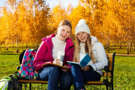 Two happy 14 years old girls in the autumn park with textbook and coffee laughing and looking at camera photo