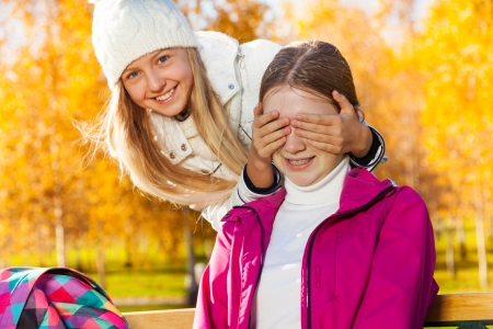 guess: Two happy 14 years old girls in the autumn park playing guess who with one girl covering face with palms and laughing