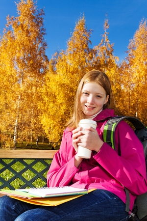 Beautiful teen 14 years old school girl sitting on the bench in autumn park holding coffee and textbooks photo