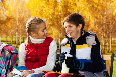 niños platicando: Niños de los pares, niño y niña sentada en el banco en el otoño de parque hablando el uno al otro después de la escuela la celebración de los libros y la taza de café Foto de archivo