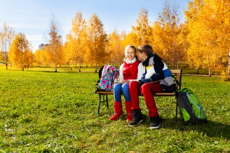 Couple children, boy whispering to girl sitting on the bench in autumn park with backpacks laying near by photo
