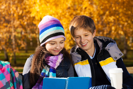Close portrait of couple children reading textbook with smile on the, boy and girl sitting on the bench in autumn park wearing warm clothes photo