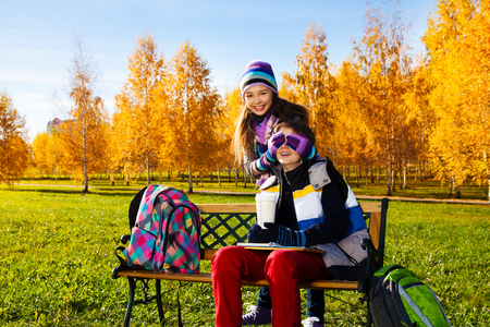 Couple children, girl covers boys face with palms and laughing making a surprise, guy sitting on the bench in autumn park Stock Photo - 24340217