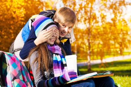 hides: Couple children, boy covers girls face with palms and laughing making a surprise, gal sitting on the bench in autumn park