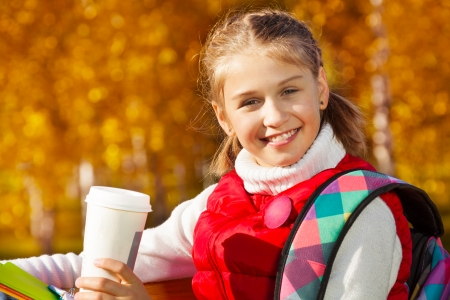 11: Close portrait of happy blond 11 years old girl with amazing smile drinking coffee sitting on the bench in the autumn park on sunny day