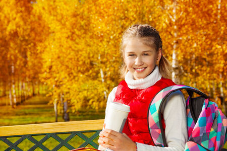 11: Happy blond 11 years old girl with amazing smile sitting on the bench, drinking coffee and wearing backpack in the autumn park on sunny day Stock Photo