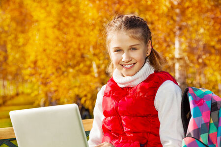 11 years: Close portrait of happy blond 11 years old girl with amazing smile sitting on the bench with laptop doing homework outside in the autumn park on sunny day