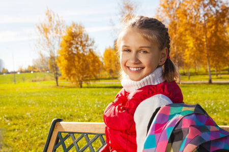 11 years: Close portrait of happy blond 11 years old girl with amazing smile turning back sitting on the bench in the autumn park on sunny day Stock Photo