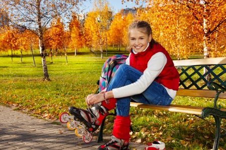 rollerblade: Happy blond 11 years old girl with amazing smile putting on roller blades sitting on the bench in the autumn park on sunny day