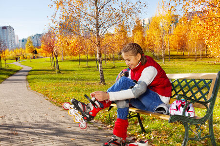 Happy blond 11 years old girl with amazing smile putting on roller blades sitting on the bench in the autumn park on sunny day photo