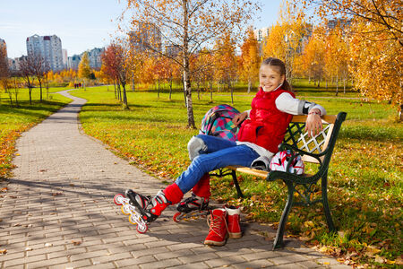 Happy blond 11 years old girl with amazing smile sitting on the bench wearing rollerblades and resting after skating in the autumn park on sunny day photo