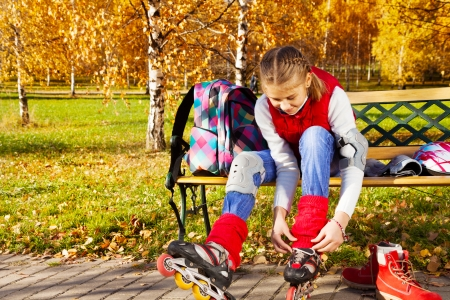 Happy blond 11 years old girl with amazing smile putting on roller blades sitting on the bench in the autumn park on sunny day, front view photo