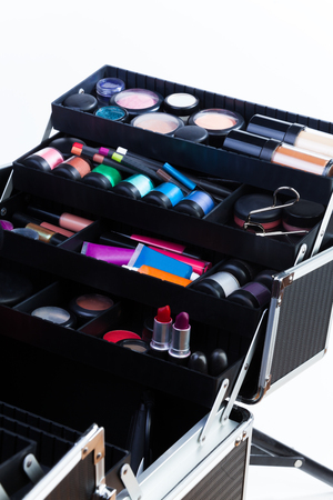 Open makeup box with professional tools such as applicator containers tubes lipsticks eyeshades