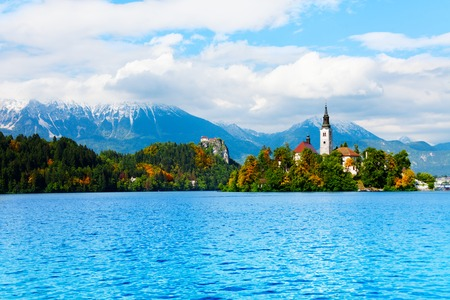 bled: Church on the small island in the middle of the Bled lake, symbol of Slovenia with Alp mountains on background