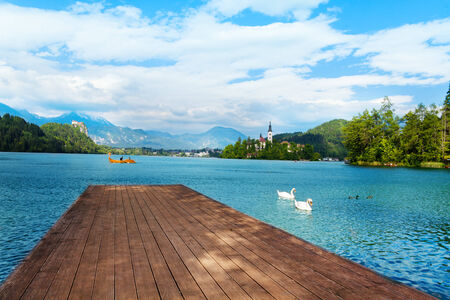 bled: Wood pier on the Bled lake in Slovenia with famous island and castle on background Stock Photo