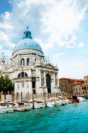 embarked: Santa Maria della Salute Basilica in Venice with boats embarked on sunny day Stock Photo