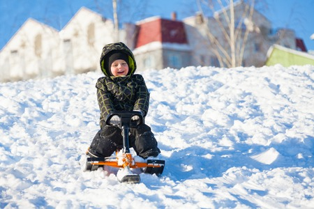 Little 3 years old boy sliding on the sledge scooter on winter day photo