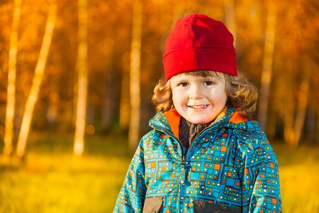 Close portrait of happy smiling three years old little boy standing on the lawn in the autumn park photo