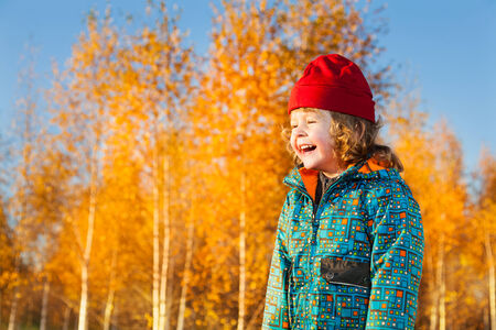 Close portrait of happy laughing three years old little boy standing on the lawn in the autumn park photo