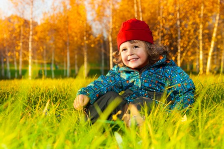 Happy 3 years old boy sit on the lawn in laugh in the autumn park  photo