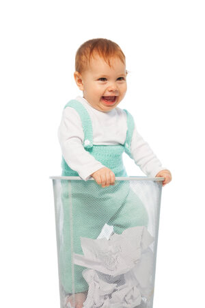 Little baby girl standing in the garbage bin with crumpled paper