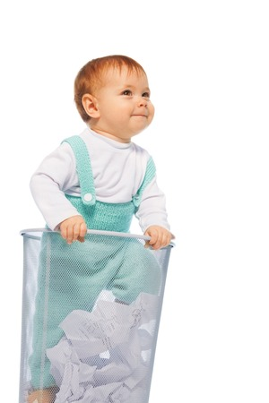 Funny little baby girl stand in the basket bin and smiling photo