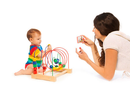 Mother photograph her little toddler boy playing with puzzle developing toy with camera on cell phone photo