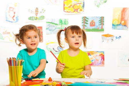 2 years old: Two little cute girls painting on creative class in kindergarten