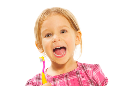 five years old: close portrait of laughing little girl standing with toothbrush isolated on white