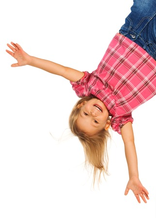Happy 4 years old girl hanging upside down isolated on white with smile on her face photo