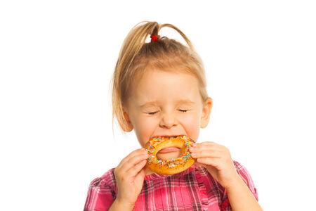 boca cerrada: Un bonito y pequeño anillo de pan muchacha mordiendo aislado en blanco con los ojos cerrados Foto de archivo
