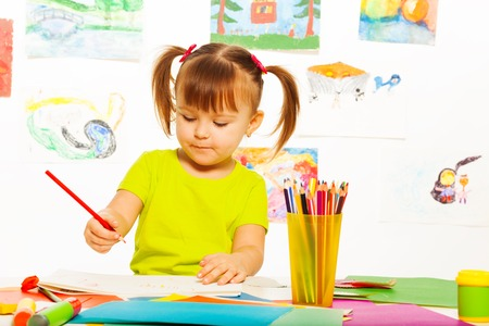 old pencil: Cute little 3 years old girl in yellow shirt and pony tails draw with pencil in the art class with images on the wall Stock Photo