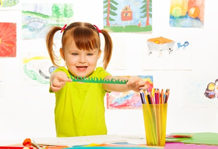 Cute little girl cutting and gluing color paper in the preschool art class Reklamní fotografie