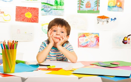 Nice bored three years old boy sitting in the class with images paper and pencils photo
