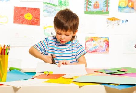 3 jaar oude jongen snijden karton papier met een schaar in voorschoolse kunst klasse