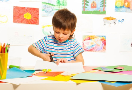 3 years old boy cutting cardboard paper with scissors in preschool art class  Stock Photo