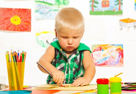 2 years old blond boy drawing with pencil on preschool art class with images on background photo